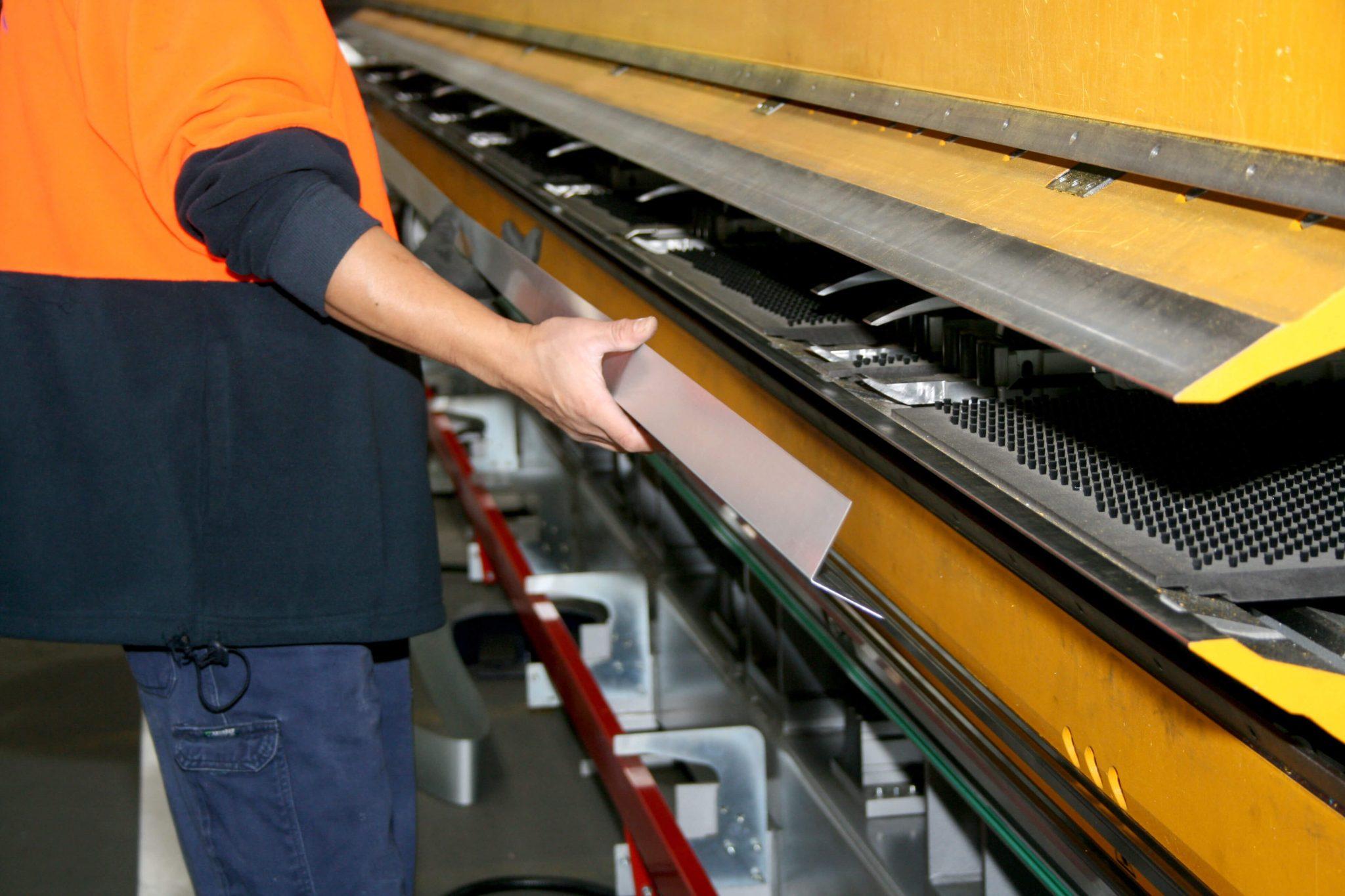 Worker working with metal sheet in Queensland sheet metal workshop