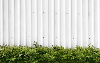 Bushes With Green Leaves In A White Metal Fence