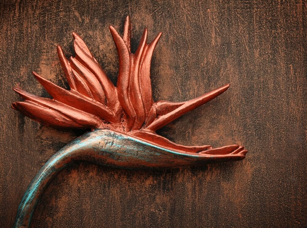 A red, blue-tinted and bronze metal Bird of Paradise flower on a brown wood-grained metal surface.