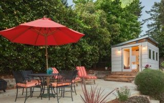 A backyard studio with outdoor dining table and red shade umbrella in the foreground