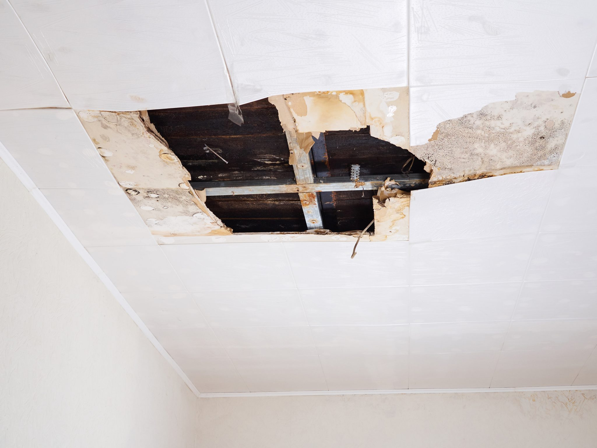Water damaged ceiling with multiple panels damaged