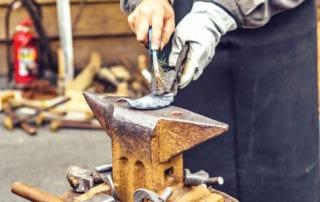 Blacksmith polishing metal piece on big metal anvil