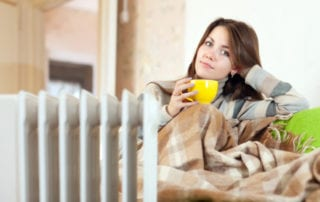 woman with yellow cup near oil heater at home