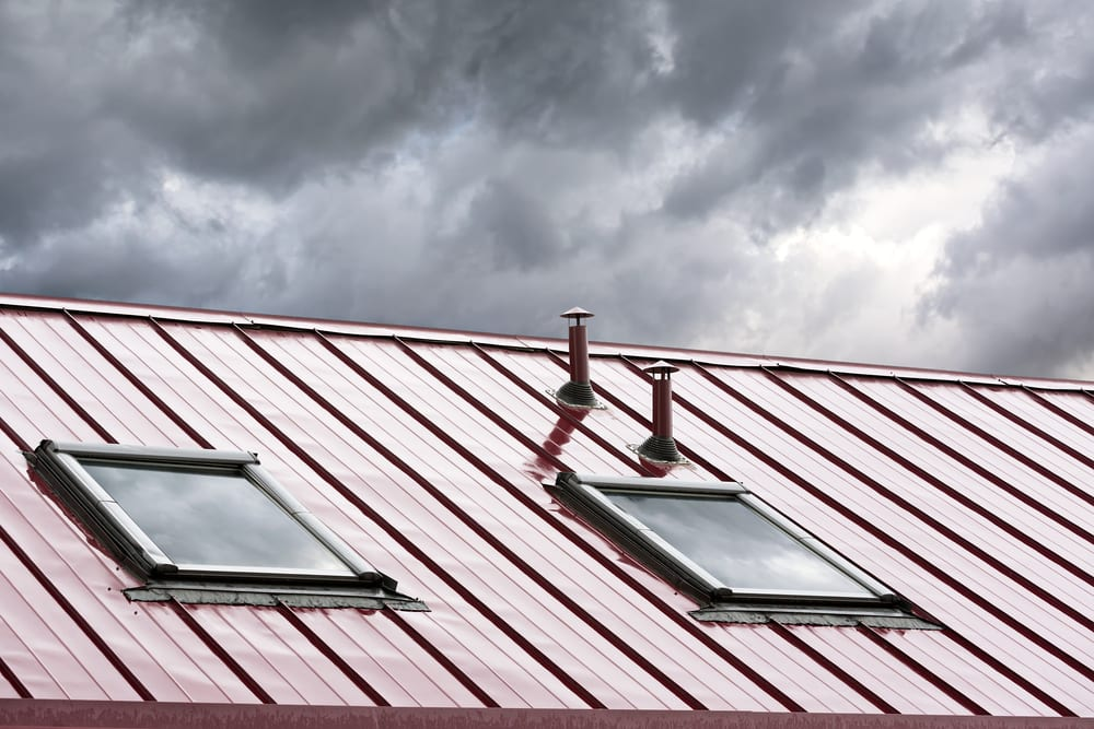 new grey metal roof with skylights against cloudy sky